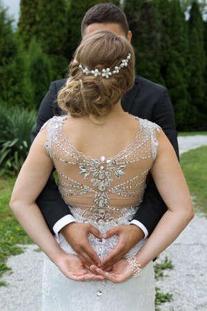 personas abrazadas: Novio que hace una muestra del corazón con sus manos mientras mantiene los brazos alrededor de su novia Foto de archivo