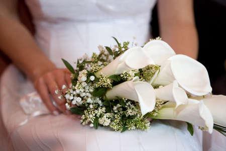Braut hält eine Hochzeit Bouquet auf dem Schoß Standard-Bild - 46711244