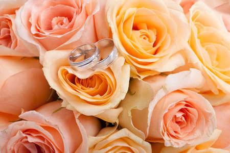 rosas blancas: los anillos de bodas de plata y un ramo de novia