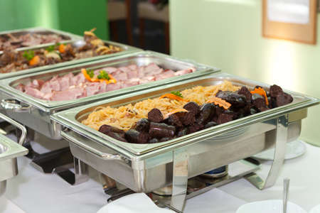 heated: Blood sausage or black pudding made with pigs blood and buckwheat porridge or rice served with stewed sauerkraut in heated trays Stock Photo