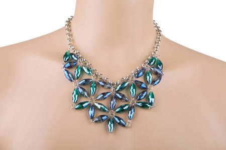 diamante: Silver statement necklace on a mannequin with blue and green rhinestones. A rhinestone or diamante is a diamond simulant made from rock crystal, glass or acrylic Stock Photo