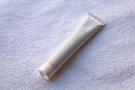 aftershave: White tube of toothpaste, cream or gel, white clean, ready for your design product (on a white towel)