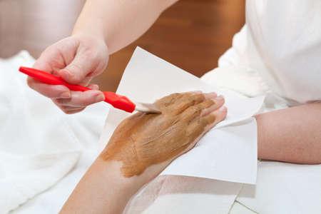 nourishing: Therapist applying nourishing mask on womans hand