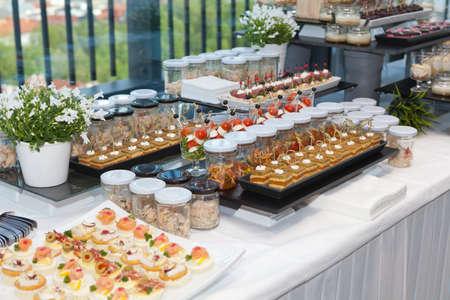 arreglo floral: Muy bien decorado mesa de banquete de catering con diferentes aperitivos de comida y aperitivos Foto de archivo