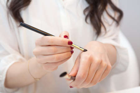 blending: Makeup artist trying new makeup brushes on her hand Stock Photo