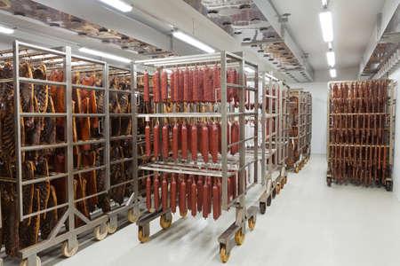 embutidos tradicionales frescos listos para el secado en un ahumadero de una industria de procesamiento de carne