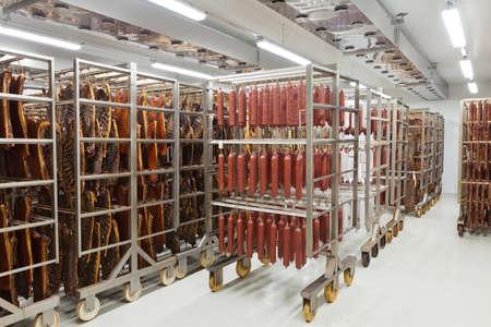 Salumi tradizionali freschi pronti per l'essiccazione in un affumicatoio di un industria della carne Archivio Fotografico - 60260267