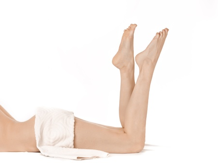 Beautiful naked female legs over white background