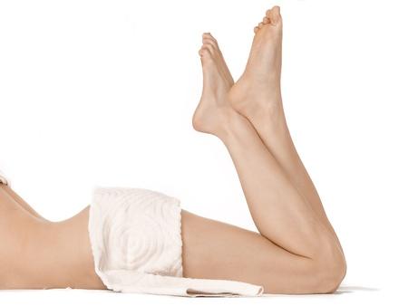Deux jambes de la femme avec crème pour le corps hydratant