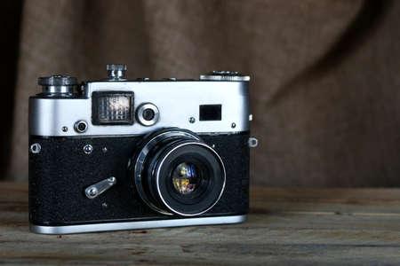 Old film camera. Vintage film photo camera on old wooden background.