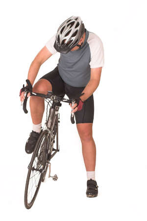 Cyclist getting onto bicycle photo