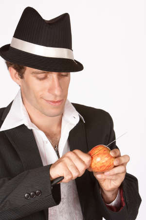 informal clothing: Man slicing apple with knife wearing a suit