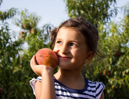 little girl with peach in hand Reklamní fotografie