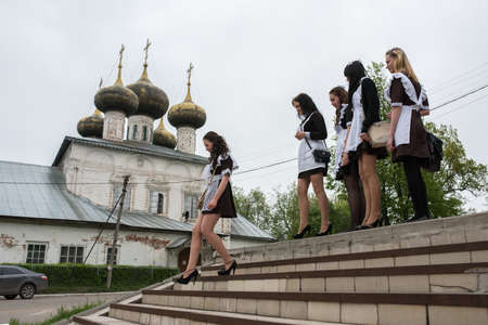 backwoods: Ustyuzhna Vologda region, Russia - May 22, 2015: schoolgirl in uniform climb the stairs on the background of white stone five-domed Orthodox church Editorial