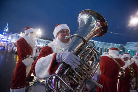 clauses: St. Petersburg, Russia - December 22, 2014: Santa Clauses march along Nevsky Prospekt, Trumpeter dressed as Santa