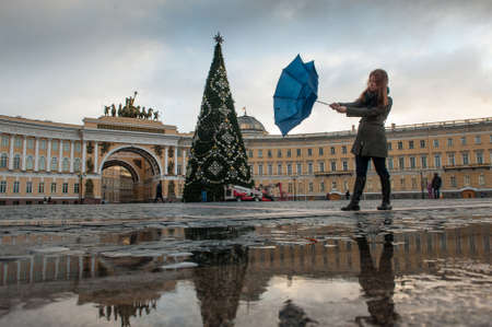 angel alone: St. Petersburg, Russia - December 7, 2015: Palace Square decorated Christmas tree, woman with a broken umbrella because strong wind