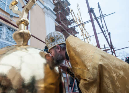St. Petersburg, Russia - December 16, 2015: Completion of the restoration of gilded crosses Prince Vladimir Cathedral in the courtyard. The priest kisses the base of the cross Editorial