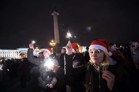 sincere girl: St.Petersburg, Russia - January 1 2015: People with sparklers in their hands celebrating Christmas and New Year at the Palace Square in the heart of the city