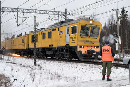 caboose: Leningrad Oblast, Russia - December 18, 2015: Train maintenance railway carries grinding rails on the stretch of road in the winter, engineer-inspector checks the quality of work