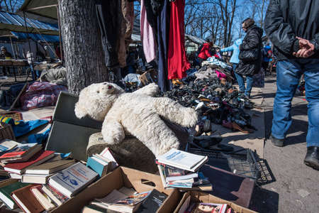 St. Petersburg, Russia - April 11, 2015: Flea market, old teddy bear toy figurine girl, books, different items laid out on the ground for sale