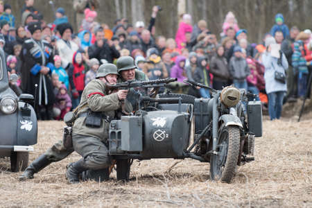 st german: St. Petersburg, Russia - April 26, 2015: Members of the military-patriotic club during the historical reconstruction of World War II battle for the Seelow Heights, German soldiers, German soldiers on a motorcycle with a sidecar