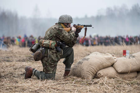 german soldier: St. Petersburg, Russia - April 26, 2015: Members of the military-patriotic club during the historical reconstruction of World War II battle for the Seelow Heights, German soldier firing a machine gun burst