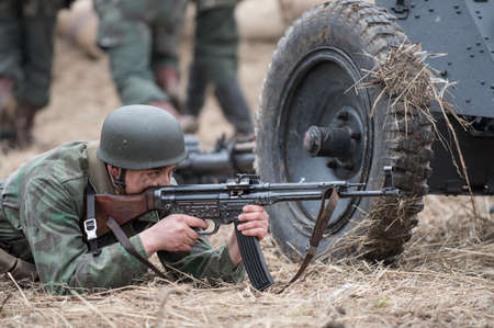 st german: St. Petersburg, Russia - April 26, 2015: Members of the military-patriotic club during the historical reconstruction of World War II battle for the Seelow Heights, German soldier firing a machine gun burst