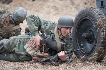 fastens: St. Petersburg, Russia - April 26, 2015: Members of the military-patriotic club during the historical reconstruction of World War II battle for the Seelow Heights, German soldier fastens to the machine cartridges
