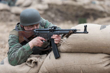 german soldier: St. Petersburg, Russia - April 26, 2015: Members of the military-patriotic club during the historical reconstruction of World War II battle for the Seelow Heights, German soldier aiming to shoot a machine gun