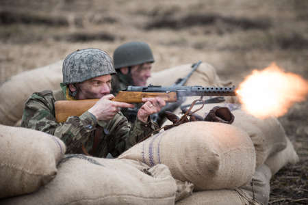 st german: St. Petersburg, Russia - April 26, 2015: Members of the military-patriotic club during the historical reconstruction of World War II battle for the Seelow Heights, German soldier firing a machine gun, a flame from the barrel of the gun Editorial