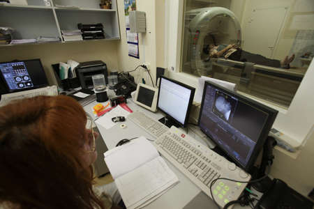 axial: St. Petersburg, Russia - September 19, 2011: An employee of the medical staff monitor patients during computed axial tomography. Diagnosis of the human brain