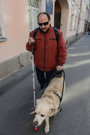 St. Petersburg, Russia - May 29, 2012: A blind man of 50 years during training walking around the city with the help of a guide dog breed Labrador on the main street. Editoriali