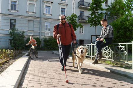 St. Petersburg, Russia - May 29, 2012: A blind man of 50 years during training walking around the city with the help of a guide dog breed Labrador on the main street.