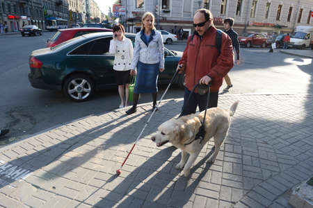 visually: St. Petersburg, Russia - May 29, 2012: A blind man of 50 years during training walking around the city with the help of a guide dog breed Labrador on the main street. Editorial