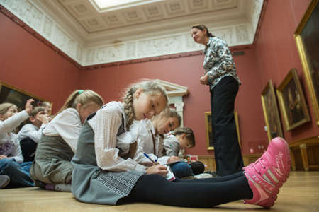 children painting: St. Petersburg, Russia - September 21, 2012: Children on an excursion to Russian Museum considered masterpieces of painting and sculpture, listen to the story guide of the works of great artists. Editorial