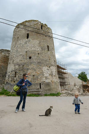 the medieval: Izborsk Pskov region, Russia - May 31, 2012: Tourists on the background of Izborsk fortress tower on a lovely sunny day. Mother and child looking at the cat. Editorial