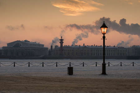 View of the frozen Neva River and the panorama of St. Petersburg with a street lamp in the foreground on a cold winter evening during sunset