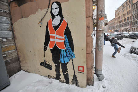 St.Petersburg, Russia - January 13, 2016: Graffiti on the wall of a residential building in the city center. Woman in uniform of janitor with a broom and a dustpan with a face of the Mona Lisa by Leonardo Da Vinci