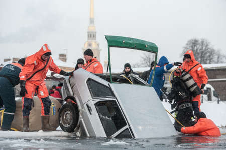 drowned: St.Petersburg, Russia - January 15, 2016: Experts rescuers Ministry of Emergency Situations are taking drowned old car from under  the ice of the Neva river in historical center of city