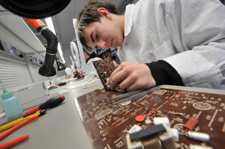 vocational: St. Petersburg, Russia - March 18, 2015: Students of vocational school in a workshop  of electrical engineering. Study and soldering of simple electric circuits. Editorial