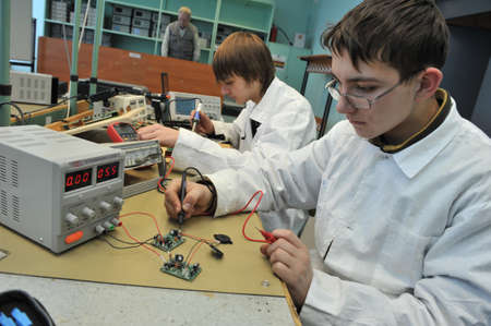 St. Petersburg, Russia - March 18, 2015: Students of vocational school in a workshop  of electrical engineering. Study and soldering of simple electric circuits. Sajtókép