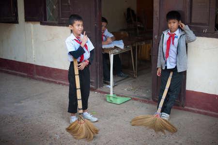 Vientiane, Laos - 11 diciembre 2013: Los estudiantes en los uniformes escolares en un descanso entre clases en el patio de la escuela jugando juegos de varios niños. Diversión, risas, sonrisas.