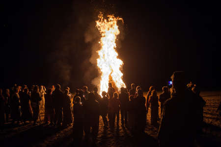 burns night: Leningrad Oblast, Russia - July 14, 2015: Big  tourist bonfire on the beach Finland Gulf during the festival. Young people dance and sing around the campfire. Deep night.