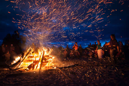 Leningrad Oblast, Russia - July 14, 2015: Big  tourist bonfire on the beach Finland Gulf during the festival. Young people dance and sing around the campfire. Deep night.