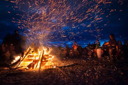 fogatas: Provincia de Leningrado, Rusia - 14 de julio de 2015: gran hoguera turista en la playa del Golfo de Finlandia durante el festival. Los jóvenes cantan y bailan alrededor de la fogata. Noche profunda.