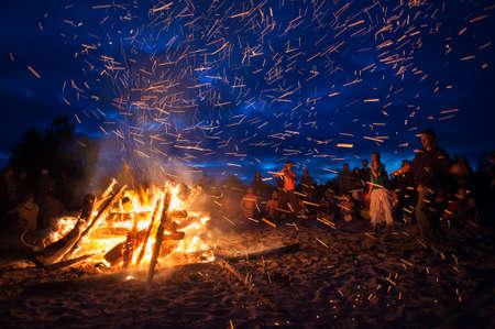 Provincia de Leningrado, Rusia - 14 de julio de 2015: gran hoguera turista en la playa del Golfo de Finlandia durante el festival. Los jóvenes cantan y bailan alrededor de la fogata. Noche profunda. Foto de archivo - 51586471