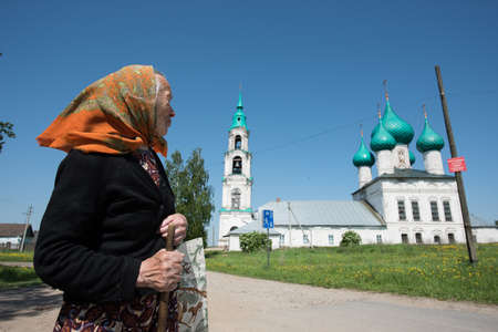 old church: Levashovo village, Yaroslavl Region, Russia - May 27, 2015: The oldest woman - a parishioner of the church after the service returns home. The Church of the Resurrection in the countryside is an architectural monument of the 18th century. Summer, sunny da