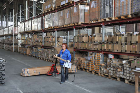 storekeeper: Novosibirsk, Russia - July 8, 2015: Storage of building materials. A female storekeeper lucky not carriage of goods packaging