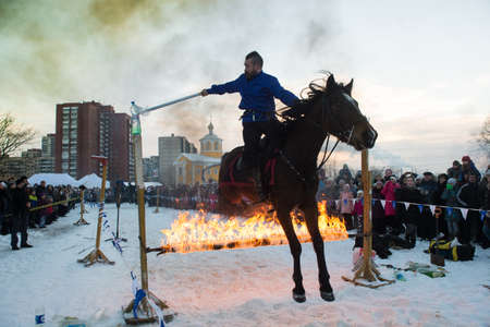 men running: St.Petersburg, Russia - January 7, 2016: The show riders on a city celebration of Christmas. Jumping through the ring of fire.