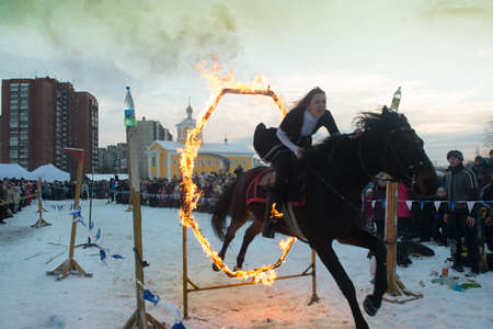 St.Petersburg, Russia - January 7, 2016: The show riders on a city celebration of Christmas. Jumping through the ring of fire.